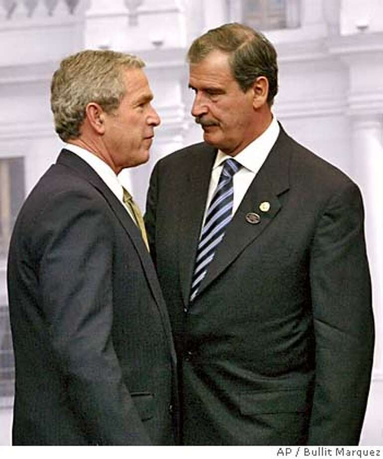 President Bush, left, and Mexican President Vicente Fox talk following the final declaration of the 2004 APEC Summit in Santiago, Chile, Sunday, Nov. 21, 2004. (AP Photo/Bullit Marquez) Ran on: 11-22-2004  President Bush (left) and Mexican President Vicente Fox talk at economic summit in Santiago, Chile. Photo: BULLIT MARQUEZ