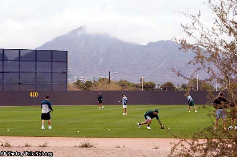 A group of Oakland Athletics' pitchers get in some early throwing with a cloud-covered Camelback Mountain in the background in Phoenix, Ariz., Friday, Feb. 14, 2003. The Athletics' pitchers and catchers are to report on Saturday with their first scheduled workout on Sunday.(AP Photo/Eric Risberg) Photo: ERIC RISBERG