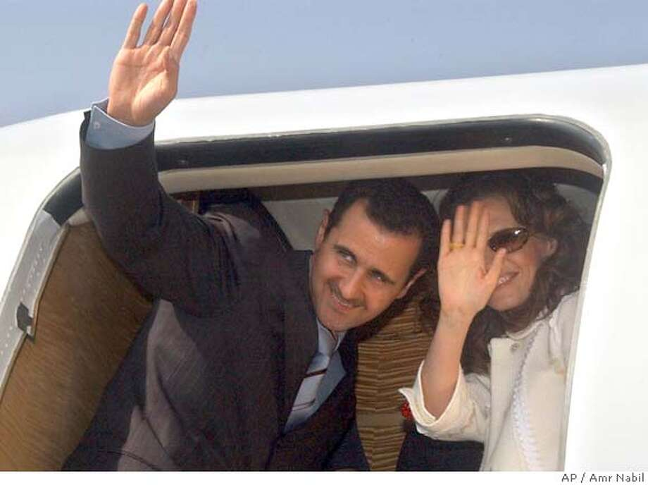Syrian President Bashar Assad, and his wife Asma, wave towards Egyptian President Hosni Mubarak and his wife, not pictured as they leave the Red sea resort of Sharm el Sheik, Egypt, Thursday, May 12, 2005. Mubarak and Assad held talks in the Red Sea resort Thursday to discuss Mideast peace and regional issues. (AP Photo/Amr Nabil) Photo: AMR NABIL