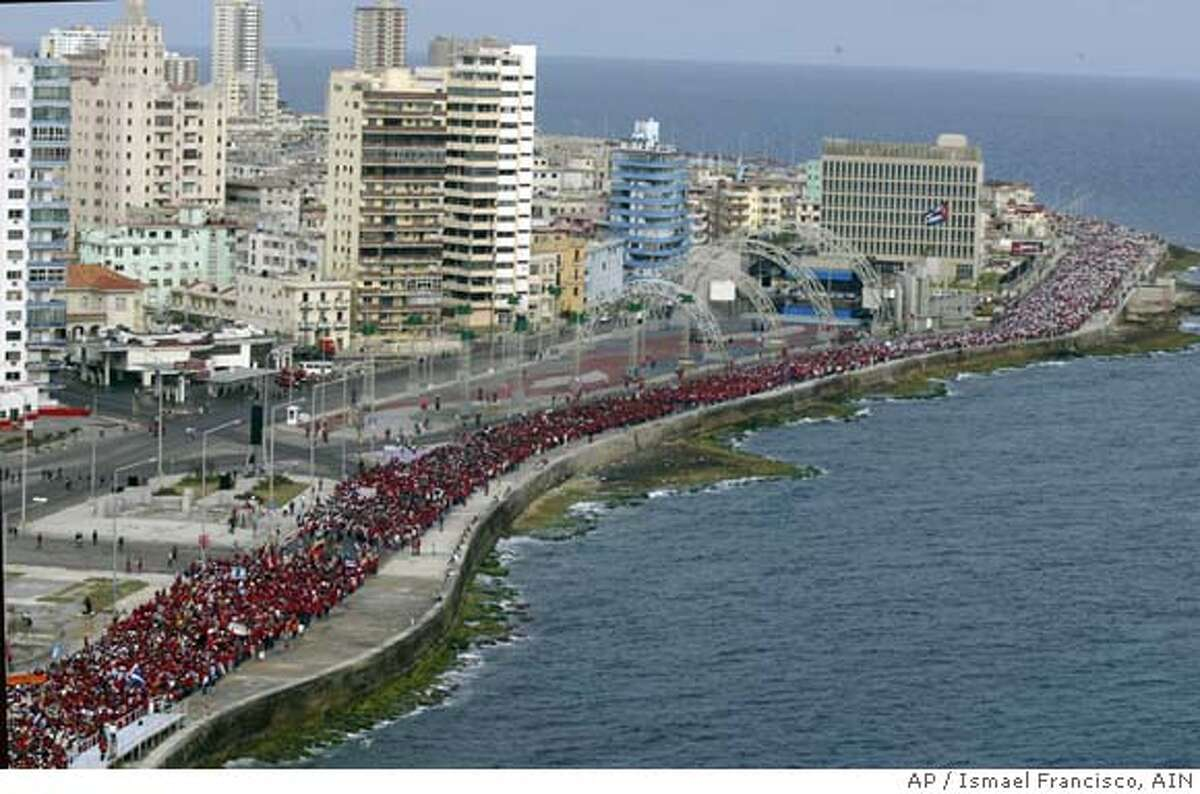 """In this photo made available by the Cuban Government's National Information Agency (AIN), hundreds of thousands of people partake in a rally, Havana, Cuba, Tuesday, May 17, 2005. Hundreds of thousands of Cubans answered Fidel Castro's call to file past the American mission early Tuesday in a """"March against Terrorism,"""" demanding that the United States arrest Cuban exile, Luis Posada Carriles, sought in a deadly airliner bombing three decades ago. (AP Photo/Ismael Francisco/AIN) **EFE OUT**"""