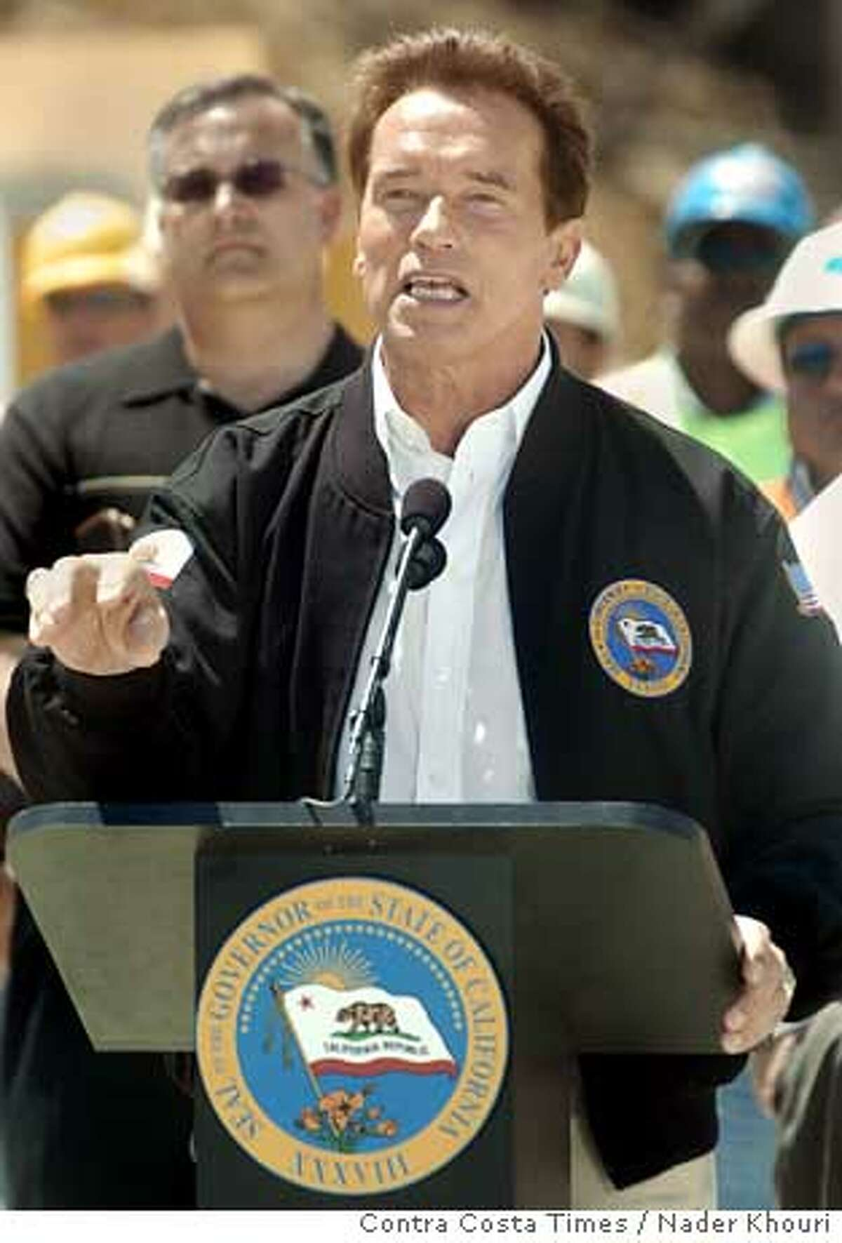 Governor Arnold Schwarzenegger speaks at a press conference in which he talked about his plans to increase transportation spending by $1.3 billion while standing on the future Highway 4 expansion under construction at Railroad Avenue in Pittsburg, Calif. on Wednesday May 12, 2005. Along with Arnold's supporters were a handful of people protesting the governor's education policy. (Contra Costa Times/Nader Khouri)