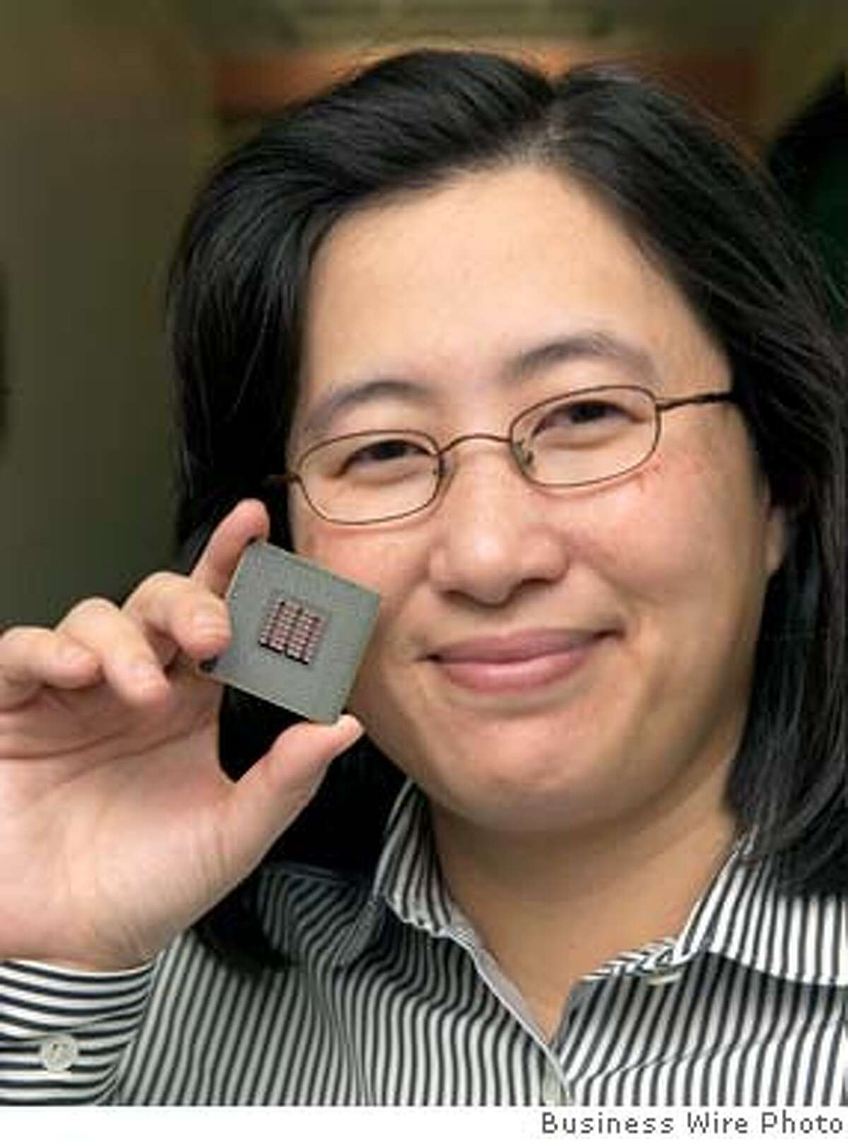"""IBM technologist Lisa Su holds the new Cell microprocessor, jointly developed by IBM, Sony and Toshiba. At the E3 conference in Los Angeles today Sony announced that Cell will power the new Sony Playstation 3 game console. Essentially a """"supercomputer on a chip"""" Cell provides vastly improved graphics and visualization capabilities, in many cases 10 times the performance of today's PC processors. (Photo: Business Wire)"""
