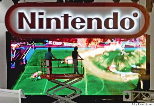 Workers on a lift move past a large projection screen running a Nintendo game as preparations for the Electronic Entertainment Exposition continue at the Los Angeles Convention Center Monday, May 16, 2005. The show runs from May 17-20. The is the trade show of the Entertainment Software Association, which allows hundreds of companies that publish interactive games for video game consoles, handheld devices, personal computers and the Internet to reach thousands of potential customers. (AP Photo/Reed Saxon) Photo: REED SAXON