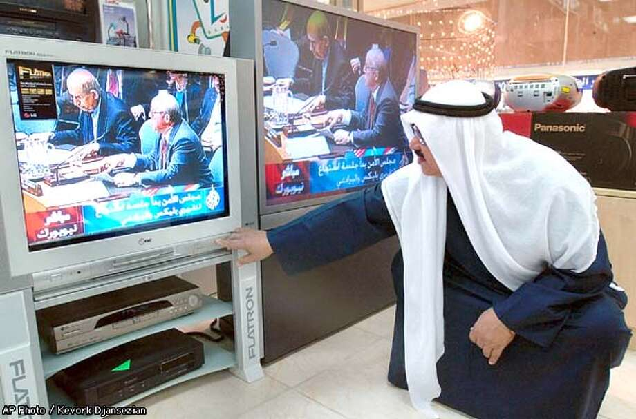 Kuwaiti shop owner Hamad Elhadad adjusts the volume on a set in his electronics store in Kuwait City while watching chief UN arms inspector Hans Blix report on Iraq to the United Nations Security Council Friday, Feb. 14, 2003. (AP Photo/Kevork Djansezian) Photo: KEVORK DJANSEZIAN