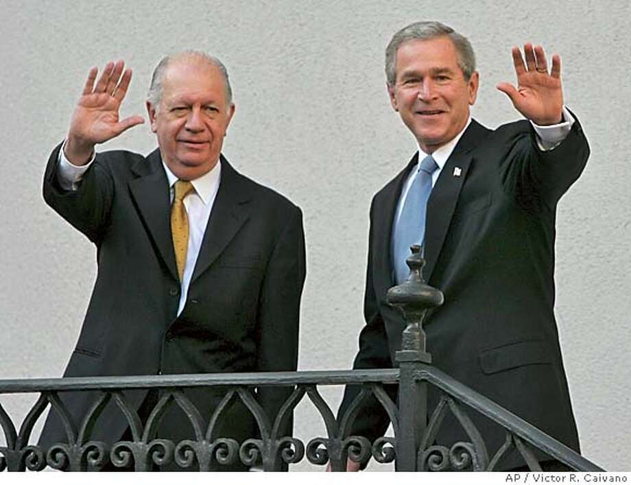 U.S. President Bush, right, waves to the media with Chilean President Ricardo Lagos, left, during a state visit at the Moneda palace in Santiago, Chile, Sunday, Nov. 21, 2004. (AP Photo/Victor R. Caivano) #MainNews#Chronicle#11/22/2004####0422479139 Photo: VICTOR R. CAIVANO