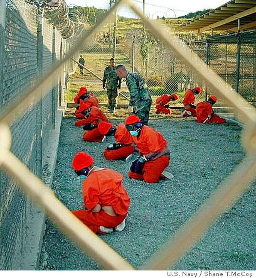 """**FILE** Suspected Taliban and al-Qaida detainees sit in a holding area at Camp X-Ray at Guantanamo Bay, Cuba, during in-processing to the temporary detention facility in this Jan. 11, 2002, file photo. Desmond Tutu, the retired South African prelate and Nobel laureate, is appearing in an off-Broadway drama which blasts the Bush administration's handling of Guantanamo Bay detainees. Tutu appeared Saturday night, Oct. 2, 2004, at a tiny theater in lower Manhattan, playing a judge in """"Guantanamo: Honor Bound To Defend Freedom."""" The play portrays the plight of British detainees at the U.S. naval base in Cuba. Standing onstage before a scene resembling holding pens at the detention camp, Tutu said he chose to appear in the play to highlight concerns about the treatment of the prisoners. (AP Photo/U.S. Navy, Shane T.McCoy) Ran on: 10-17-2004  Detainees at Guantanamo Bay, Cuba, two years ago. A JAN. 11, 2002 FILE FHOTO BookReview#BookReview#Chronicle#11-21-2004#ALL#2star#e6#0422390459 BookReview#BookReview#Chronicle#11-21-2004#ALL#2star#e6#0422390459 BookReview#BookReview#Chronicle#11-21-2004#ALL#2star#e6#0422390459 BookReview#BookReview#Chronicle#11-21-2004#ALL#2star#E1#0422390459 Photo: SHANE T. MCCOY"""
