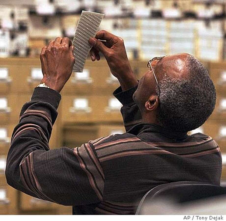 A board of elections worker looks closely at an absentee ballot at the Cuyahoga County Board of Elections Tuesday, Nov.2, 2004, in Cleveland. (AP Photo/Tony Dejak) Insight#Insight#Chronicle#11/21/2004##2star##0422446593 Photo: TONY DEJAK