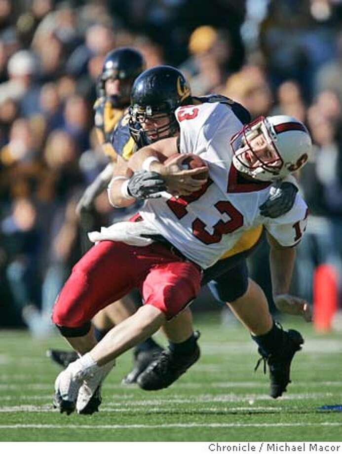 """Stanford's 13- T.C. Ostrander is sacked by Cal's 90- Ryan Riddle in the 2nd quarter. The 107th Big Game, Stanford and Cal College Football. Cal keeps the """"Axe"""" beating Stanford 41-6.  11/20/04 Berkeley, CA Michael Macor / San Francisco Chronicle Photo: Michael Macor"""
