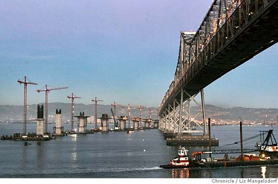 bridge040_lm  Event on 11/22/04 in Yerba Buena island.  The eastern span of the Bay Bridge, with the cranes where the new span is being constructed. A tug pushes a boat under the span at bottom right. This photo is from Yerba Buena Island.  Liz Mangelsdorf / The Chronicle MANDATORY CREDIT FOR PHOTOG AND SF CHRONICLE/ -MAGS OUT Nation#MainNews#Chronicle#11/23/2004#ALL#5star##0422481222 Photo: Liz Mangelsdorf