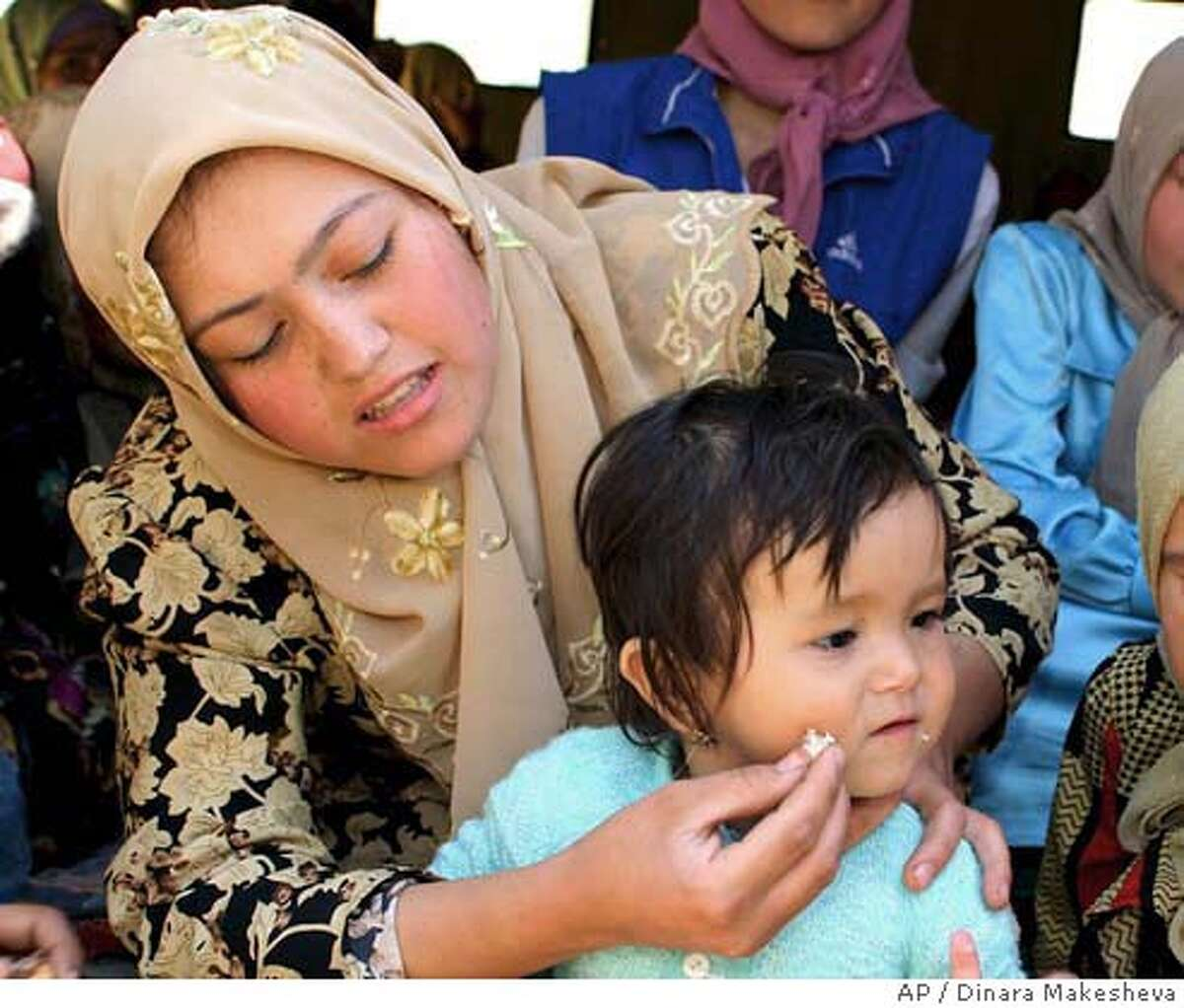 An Uzbek woman from Andijan, feeds her child at a refugee camp near Jalal-Abad region, some 600 kilometers (370 miles) south of the capital Bishkek, at the border with Uzbekistan, Monday, May 16, 2005. Kyrgyz authorities had to open a refugee camp at the border with Uzbekistan after hundreds of people from Andijan region arrived escaping the armed clashes. (AP Photo/ Dinara Makesheva)
