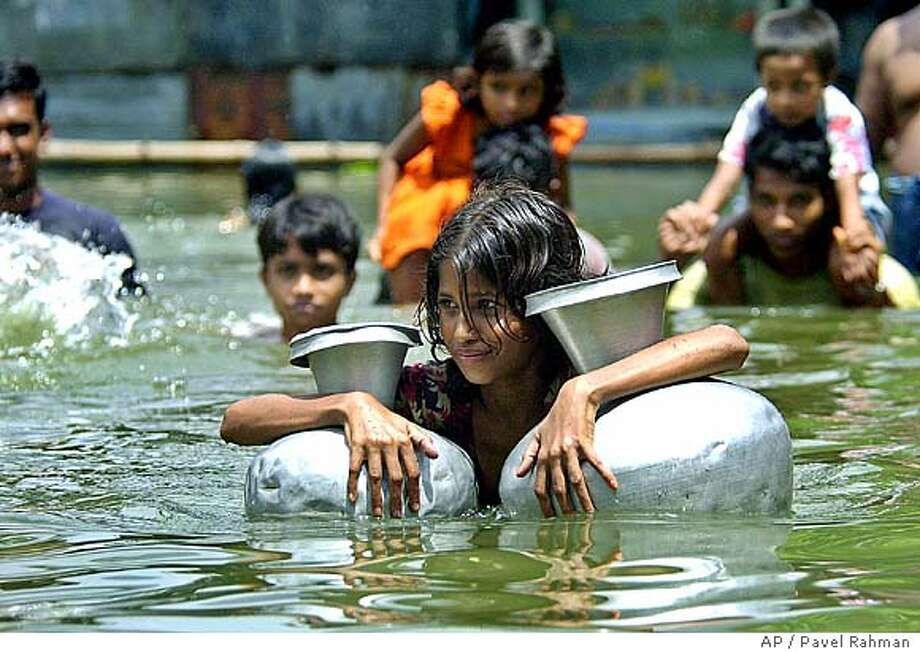 A villager tries to collect drinking water at Demra village, 15 kilometers (9 miles) south of Dhaka, Bangladesh, Monday, July 26, 2004. The death toll due to monsoon flooding has neared 950 and affected millions in South Asia. (AP Photo/Pavel Rahman) Ran on: 07-27-2004  A villager tries to collect drinking water at Demra village, 9 miles south of Dhaka, Bangladesh. Insight#Insight#Chronicle#11/21/2004#ALL#2star##0422216236 Photo: PAVEL RAHMAN