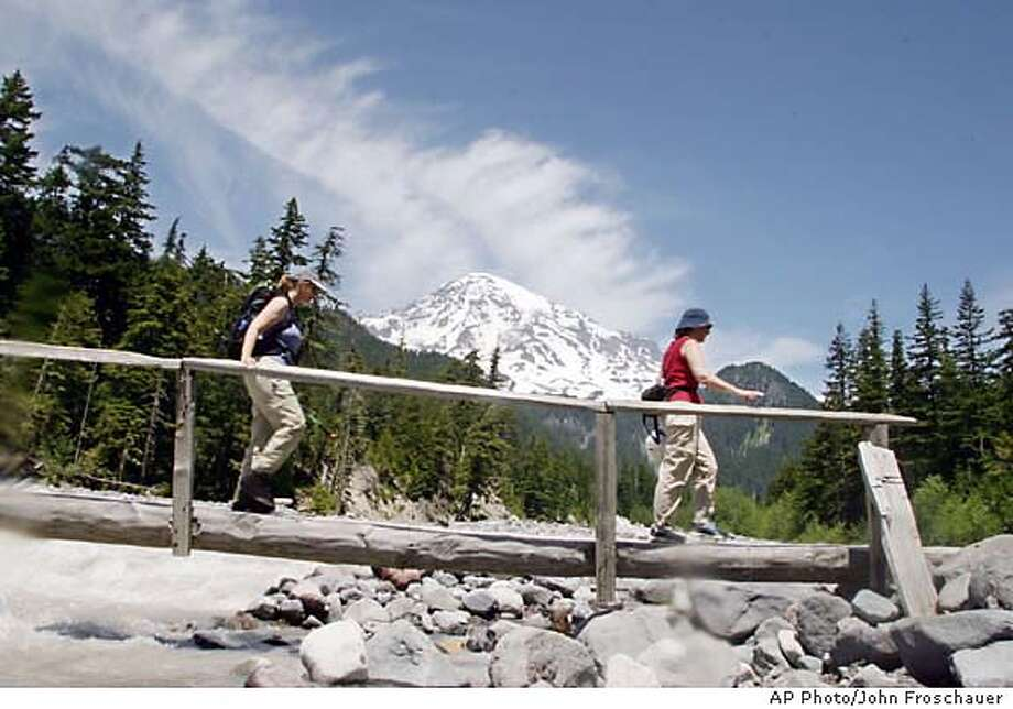 ** FOR IMMEDIATE RELEASE ** Two unidentified hikers cross a bridge over the Nisqually River under the shadow of Mt. Rainier on a section of the Wonderland Trail in Mt. Rainier National Park, Wash., June 17, 2003. About 8,000 or so people trek the trail each year, one of the most breathtaking backpacking trails in the nation. (AP Photo/John Froschauer) CAT FOR IMMEDIATE RELEASE Photo: JOHN FROSCHAUER