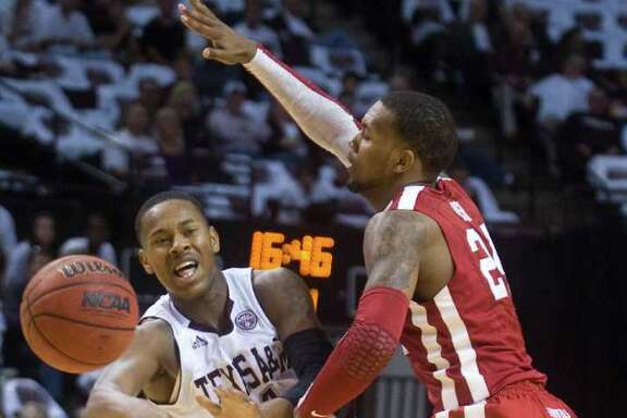 Texas A&M's Keith Davis falls backward as he makes a pass while being guarded by Oklahoma's Romero Osby during the first half of an NCAA college basketball game at Reed Arena in College Station, Texas, Saturday, Jan. 21, 2012.  (AP Photo/Bryan-College Station Eagle, Stuart Villanueva)