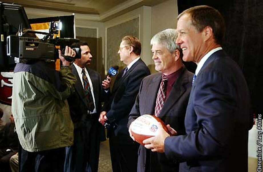 Dennis Erickson,center, shakes hands with Terry Donahue, General Manager of the niners, for the cameras, as John York, owner of the team answers questions for television, during a press conference, Wed. Feb.12,03, in San Francisco.  San Francisco Chronicle Photographer Lacy Atkins Photo: LACY ATKINS