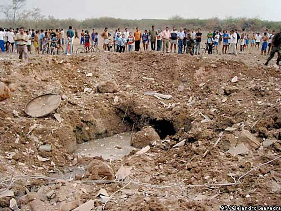 Residents watch the crater left by a bomb that exploded in Neiva, 150 miles southwest of Bogota, Colombia, Friday, Feb. 14, 2003. The explosion went off when police searched a house for explosives, killing fifteen people and wounding about 30, authorities said. (AP Photo/Alejandro Saavedra, Diario del Huila) Photo: ALEJANDRO SAAVEDRA