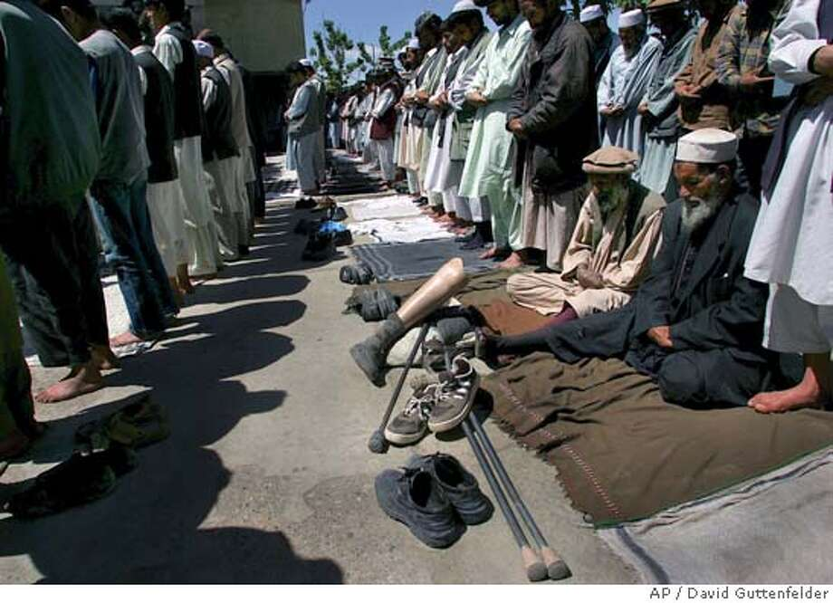 Afghan men leave their shoes next to the crutches and prosthetic limbs of two landmine victims during noon prayers at a mosque in central Kabul, Afghanistan Friday May 13, 2005. Protests continued for a forth day in the provinces of Afghanistan while Kabul remained quiet in reaction to a reported abuse of Islam's holy book at the U.S. jail in Guantanamo Bay. (AP Photo/David Guttenfelder) Photo: DAVID GUTTENFELDER