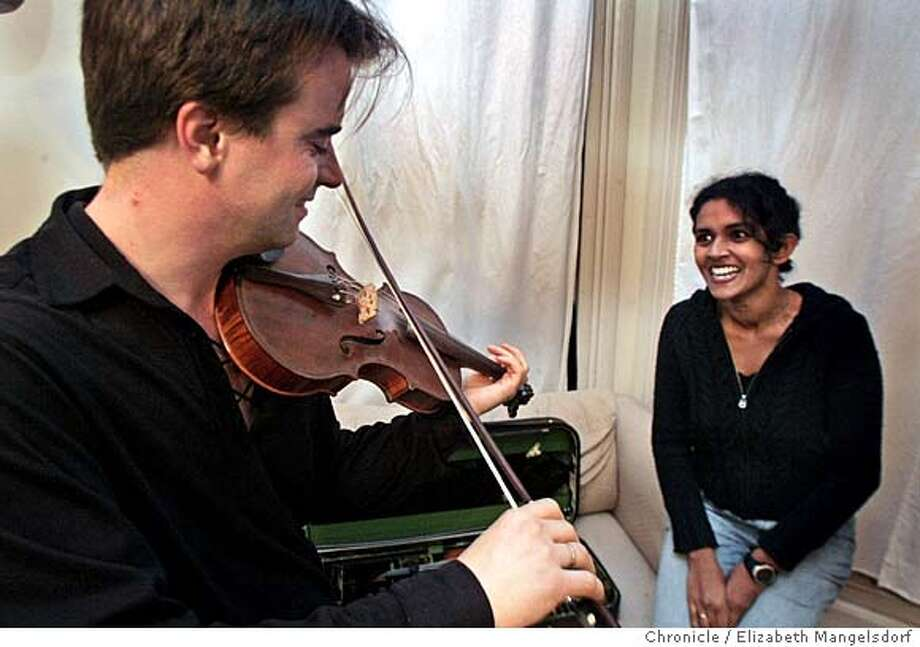 """Event on 11/10/04 in San Francisco. Poet Pireeni Sundaralingam watches her husband, Colm O'rRain, play the violin at their home on Castro St. in San Francisco. They are the producers of a new CD called """"Bridge Across the Blue"""".  Liz Mangelsdorf / The Chronicle Photo: Liz Mangelsdorf"""