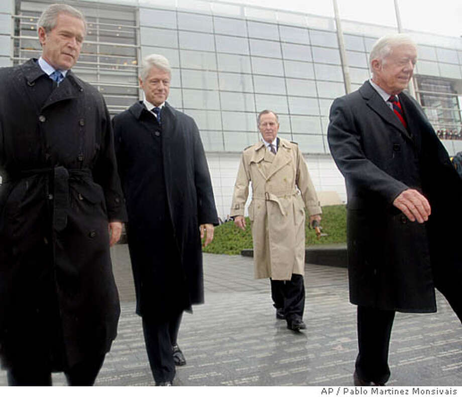 President George W. Bush, left to right, former President Bill Clinton, former President George H.W. Bush, and former President Jimmy Carter, walk from the William J. Clinton Presidential Center to the podium during opening ceremonies in Little Rock, Ark., Thursday, Nov. 18, 2004. The $165 million glass-and-steel center will be the home to Clinton's library collection of more than 80 million presidential items. (AP Photo/Pablo Martinez Monsivais) Photo: PABLO MARTINEZ MONSIVAIS