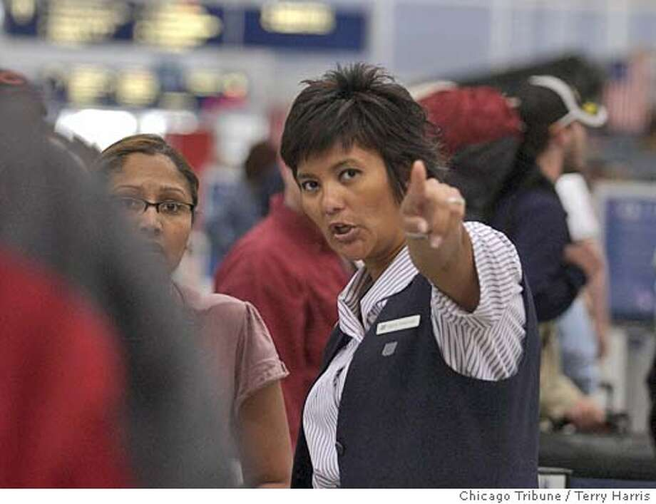 A customer service employee for United Airlines durects passengers to ticket lines Wednesday, May 11, 2005, at O'Hare International Airport in Chicago. While trying to emerge from bankruptcy, United, the nation's second-largest airline, is seeking approval to replace existing contracts with mechanics and machinists with its own lower-cost versions. But with three employee groups threatening to strike over the airline's latest proposal, even the hint of a strike can be costly to the carrier in terms of lost bookings, and if workers walk for any length of time, they can put carriers out of business.(AP Photo/Chicago Tribune, Terry Harris) CHICAGO OUT ROCKFORD REGISTER OUT NO MAGS NO TV Photo: TERRY HARRIS