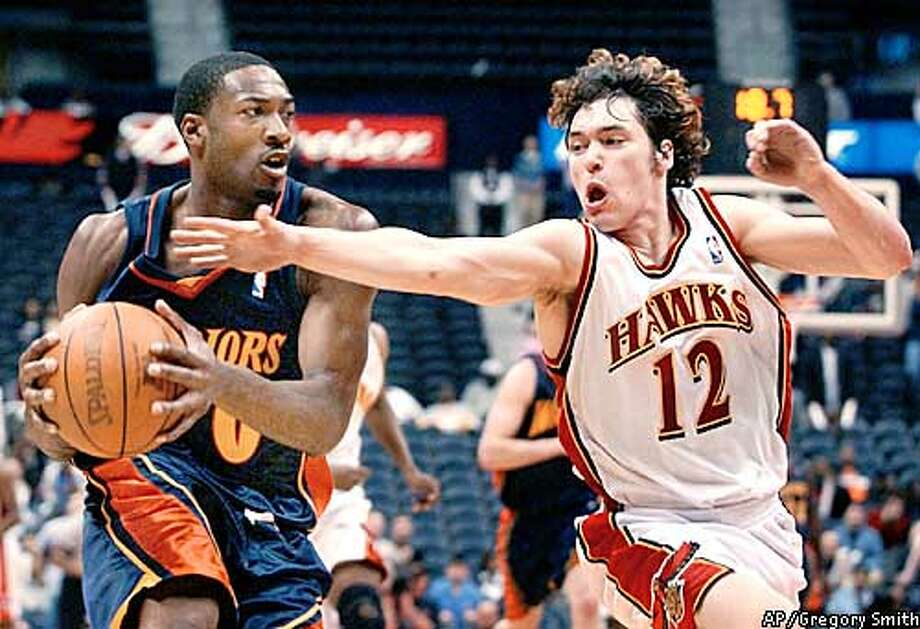 Golden State Warriors' Gilbert Arenas (0) makes a last-minute steal and drives for the go-ahead basket as Atlanta Hawks' Dan Dickau (12) tries to reclaim the ball during the fourth quarter, Tuesday, Feb. 11, 2003, at Philips Arena in Atlanta. The Warriors defeated the Hawks 116-113. Arenas had 37 points for the night. (AP Photo/Gregory Smith) Photo: GREGORY SMITH
