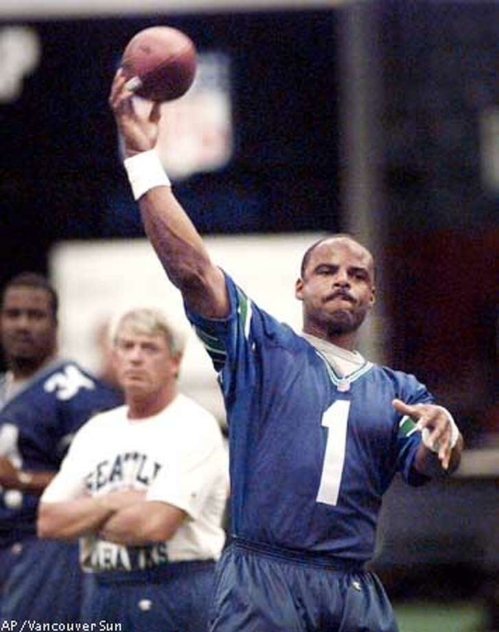 Seattle Seahawks' Warren Moon tosses the ball while being watched by coach Dennis Erickson during football practice in Vancouver, British Columbia on Friday, Aug. 14, 1998. The Seahawks meet the San Francisco 49ers in an NFL exhibition game on Saturday. (AP Photo/Vancouver Sun)