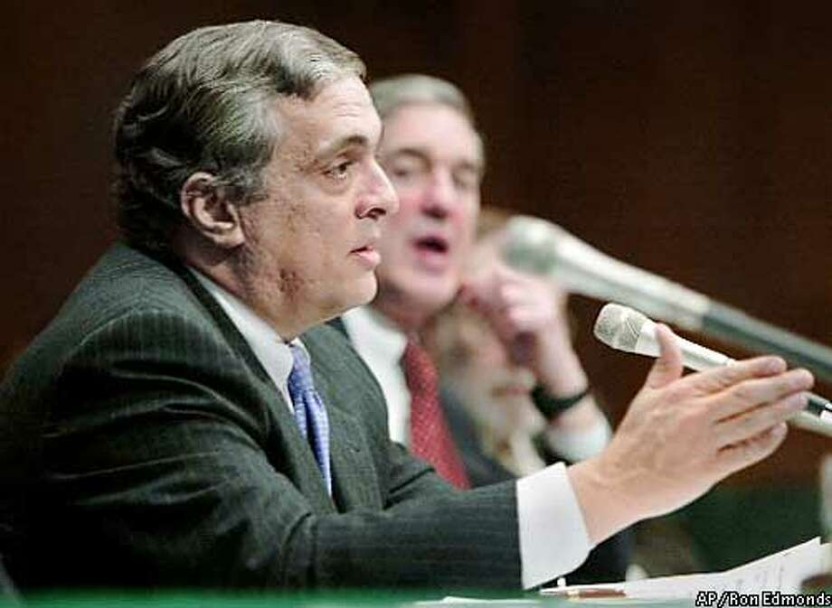 CONGRESS TERRORISM CIA Director George Tenet, left, testifies, as and FBI Director Robert Mueller, background, watches Tuesday, Feb. 11, 2003, before the Senate Intelligence Committee in Washington. Tenet and Mueller say al-Qaida still poses the greatest terror threat to America, but that their agencies are far better prepared to detect and head off attacks than they were before Sept. 11, 2001. (AP Photo/Ron Edmonds)