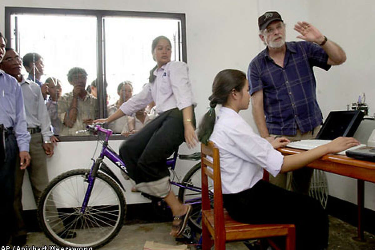 Lee Thorn, right, a Vietnam veteran and founder of San Francisco's Jhai Foundation, explains to Laotian schoolgirls how the world's first wireless, bicycle-powered PC will operate. Associated Press photo by Apichart Weerawong