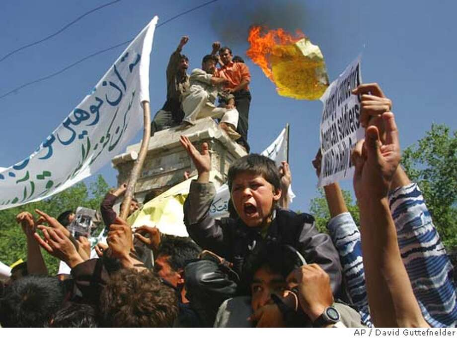 """Afghan students toss a burning paper with a drawing of U.S. President George W. Bush next to the words """"Death to Bush!"""" as protesters rally in Kabul, Afghanistan Thursday May 12, 2005. A day after riots in an eastern city left four people dead, more than 200 young men marched from a dormitory block as news of a reported abuse of Islam's holy book at the U.S. jail in Guantanamo Bay spread to the capital. (AP Photo/David Guttefnelder) Photo: DAVID GUTTENFELDER"""