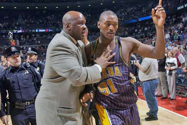 Ron Artest is lead off the court by Chuck Person, Pacers special consultant after a brawl near the end of the game.Detroit Pistons vs Indiana Pacers, November 19, 2004, Palace of Auburn Hills, Mi. (The Detroit News / Clarence Tabb, Jr.)