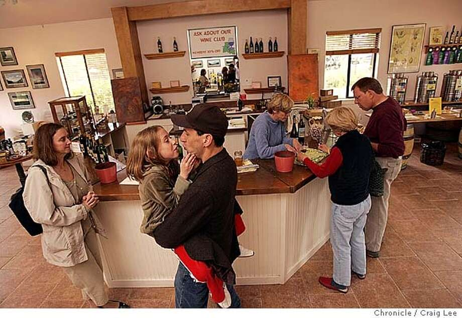 The wine tasteroom of the Anderson Valley Wine Experience in Boonville across from the Boonville Hotel. They feature three wineries, Philo Ridge, Claudia Springs and Raye's Hill, all from the Anderson Valley region. Photo of Arthur Russell in the foreground with his daughter, Delaney Russell, 8. Linda Petrocchi (far left), Delaney's mother and Arthur's wife. They are from Nutley, New Jersey. Heather McKelvey, winemaker for Philo Ridge, behind the counter, serving Larry Salyer and his wife, Tanya Salyer from Kansas City, MO.  Event on 10/26/04 in Boonville. Craig Lee / The Chronicle Photo: Craig Lee