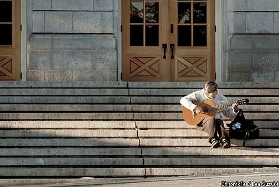 Rommel Samson, UC Berkeley music major, junior; enjoys the last rays of the sun as he plays his guitar on Sunday afternoon on the steps of Wheeler Hall on the UC Berkeley campus. Photo By Lea Suzuki/San Francisco Chronicle Photo: LEA SUZUKI