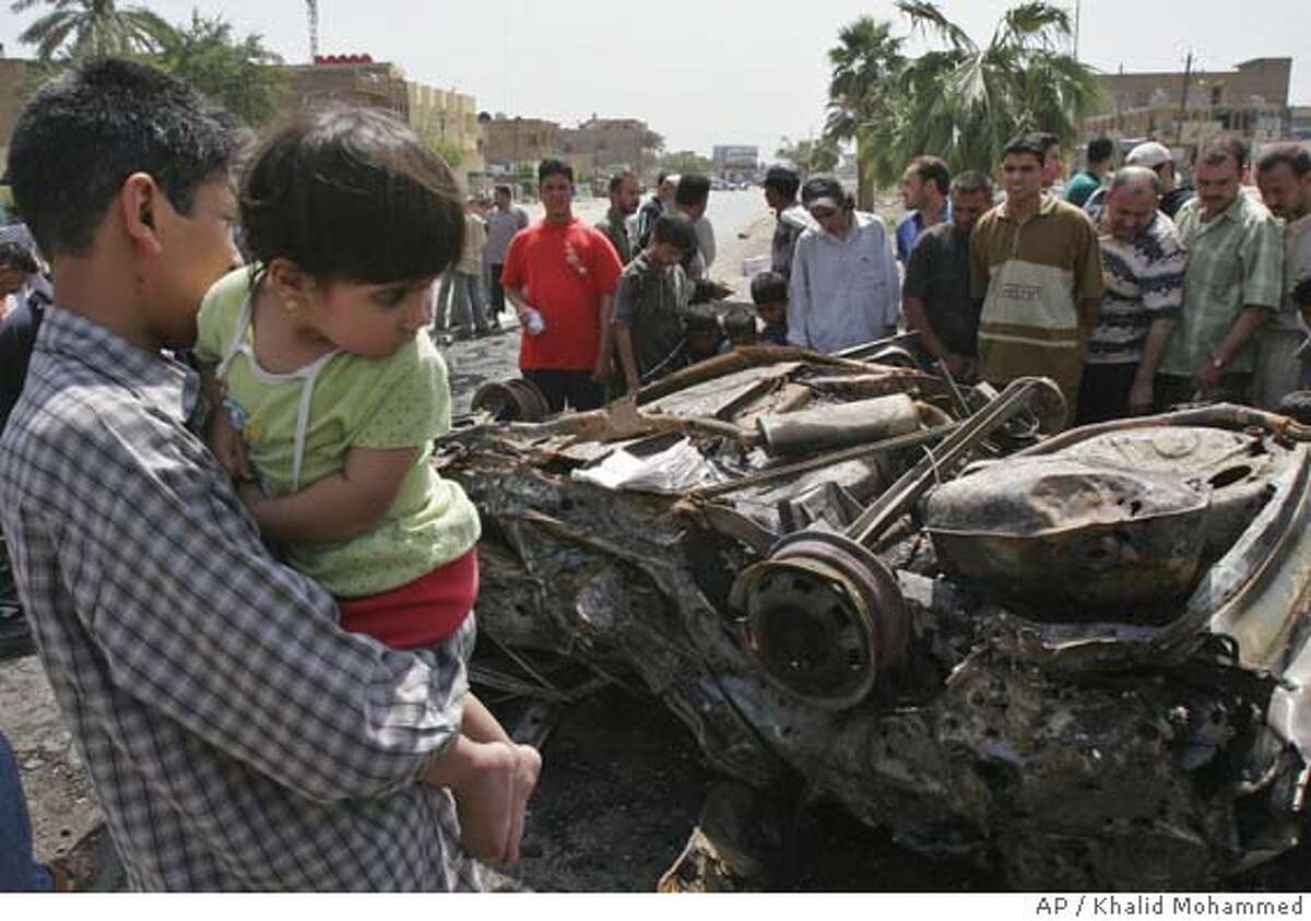 Iraqis look at the scene after a car bomb attack in Dora, Baghdad, Iraq, Wednesday, May 11, 2005. The blast in Dora near a police station killed three and wounded nine civilians. (AP Photo/Khalid Mohammed)