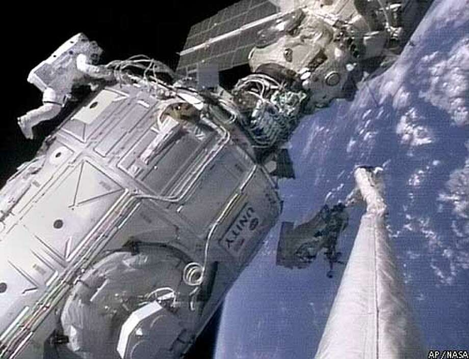 Orbiting above Earth, astronauts Jerry Ross, left, and Jim Newman work on the international space station module, Unity, Wednesday, Dec. 9, 1998 in this image from NASA television. (AP Photo/NASA TV)