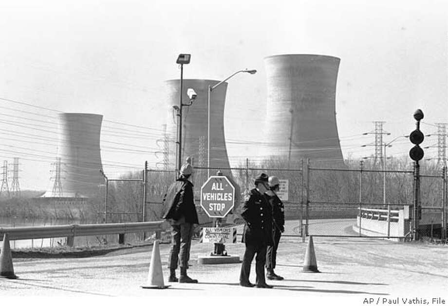 ** ADVANCE FOR SUNDAY, MARCH 28 AND THEREAFTER - FILE ** A Pennsylvania State policeman and plant security guards stand outside the closed front gate to the Metropolitan Edison Nuclear Power Plant on Three Mile Island near Harrisburg, Pa. after the plant was shut down following an accident in the plant in this March 23, 1979 black-and-white file photo. A quarter century after the country's worst nuclear accident, the atomic power industry is talking about revival. Yet no one can predict when a new reactor will be built and perceptions about safety, uncertain economics and a new specter _ terrorism _ still haunts the industry. (AP Photo/Paul Vathis, Files) Photo: PAUL VATHIS