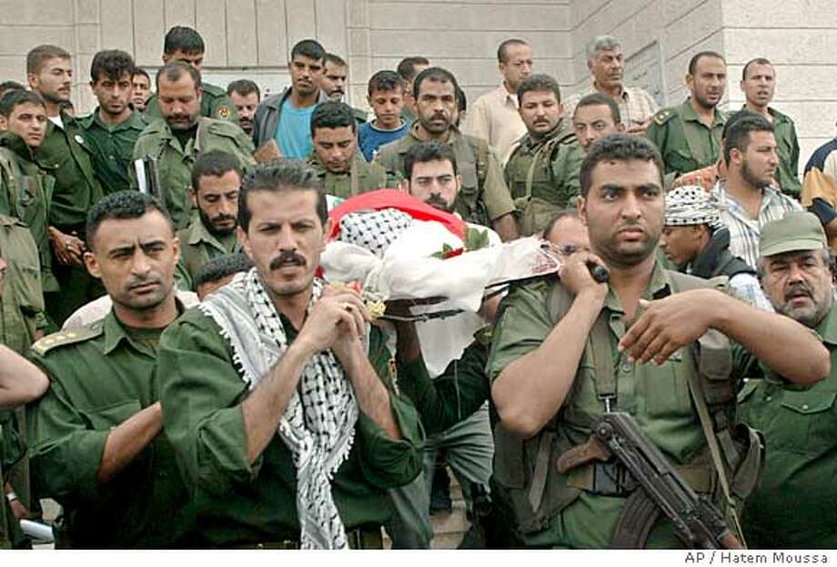 Bodyguards of late Palestinian leader Yasser Arafat carry the body of their colleague, Kamal Abu Gheinas, during his funeral in Gaza city, Monday, Nov. 15, 2004. Abu Gheinas was killed Sunday after gunmen firing assault rifles burst into a tent in Gaza City where Interim Palestinian leader Mahmoud Abbas was greeting people mourning Arafat. (AP Photo/Hatem Moussa) Ran on: 11-16-2004  Security officers carry the body of colleague Kamal Abu Gheinas, who was killed Sunday during gunfire at a memorial service for Yasser Arafat in Gaza City. Photo: HATEM MOUSSA
