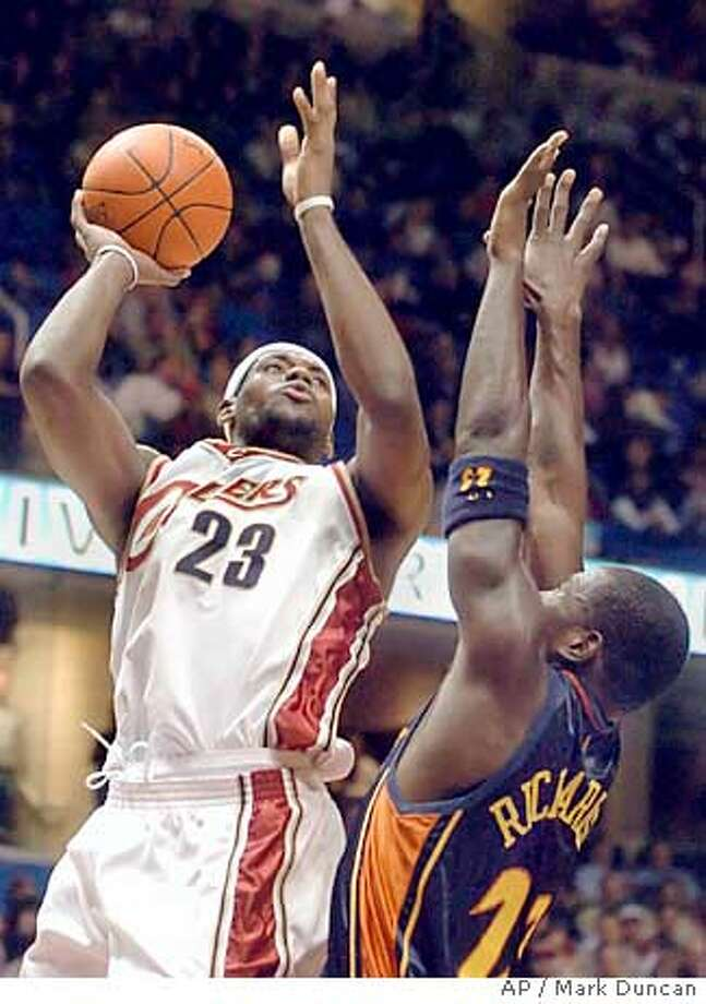 Cleveland Cavaliers' LeBron James, left, shoots over Golden State Warriors' Jason Richardson in the third quarter of Cleveland's 99-88 win Monday, Nov. 15, 2004, in Cleveland. James scored 33 points to lead the Cavaliers while Richardson led Golden State with 27. (AP Photo/Mark Duncan) Ran on: 11-16-2004  LeBron James, who scored 33 points, rises over Jason Richardson for a shot. Ran on: 11-16-2004  LeBron James, who scored 33 points, rises over Jason Richardson for a shot. Photo: MARK DUNCAN