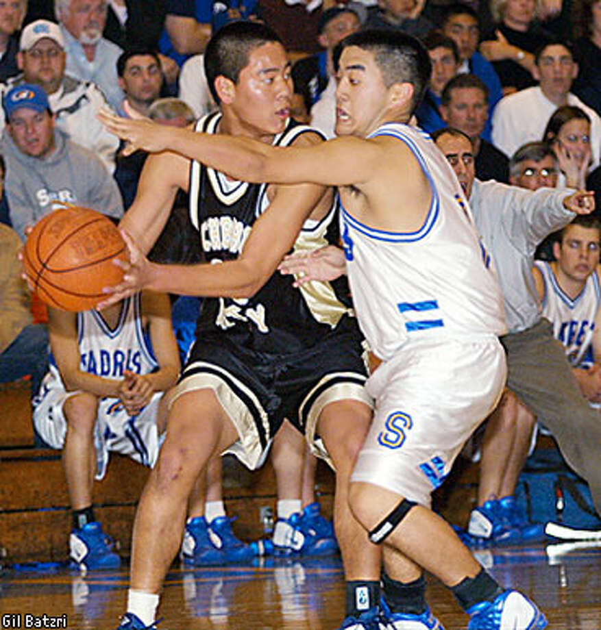 Archbishop Mitty's Martin Wan, left, looks for an open man as Serra's Mike Nishiiwa defends in Serra's close victory over Mitty on Friday night. Photo by Gil Batzri, special to SFGate.com
