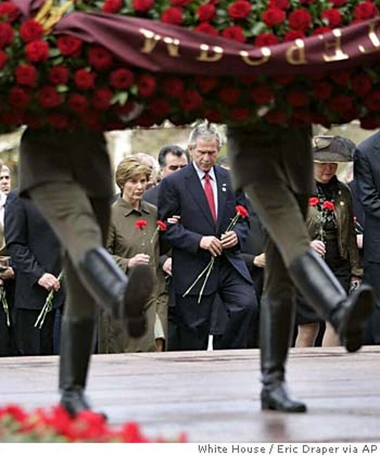 In this image provided by the White House, President Bush, second from right, first lady Laura Bush, center left, and others walk behind a line of soldiers in a wreath laying ceremony at the Tomb of the Unknown Soldier at the Kremlin Wall in Moscow, Monday, May 9, 2005, commemorating the 60th anniversary of the end of World War II. (AP Photo/White House, Eric Draper) Photo: ERIC DRAPER