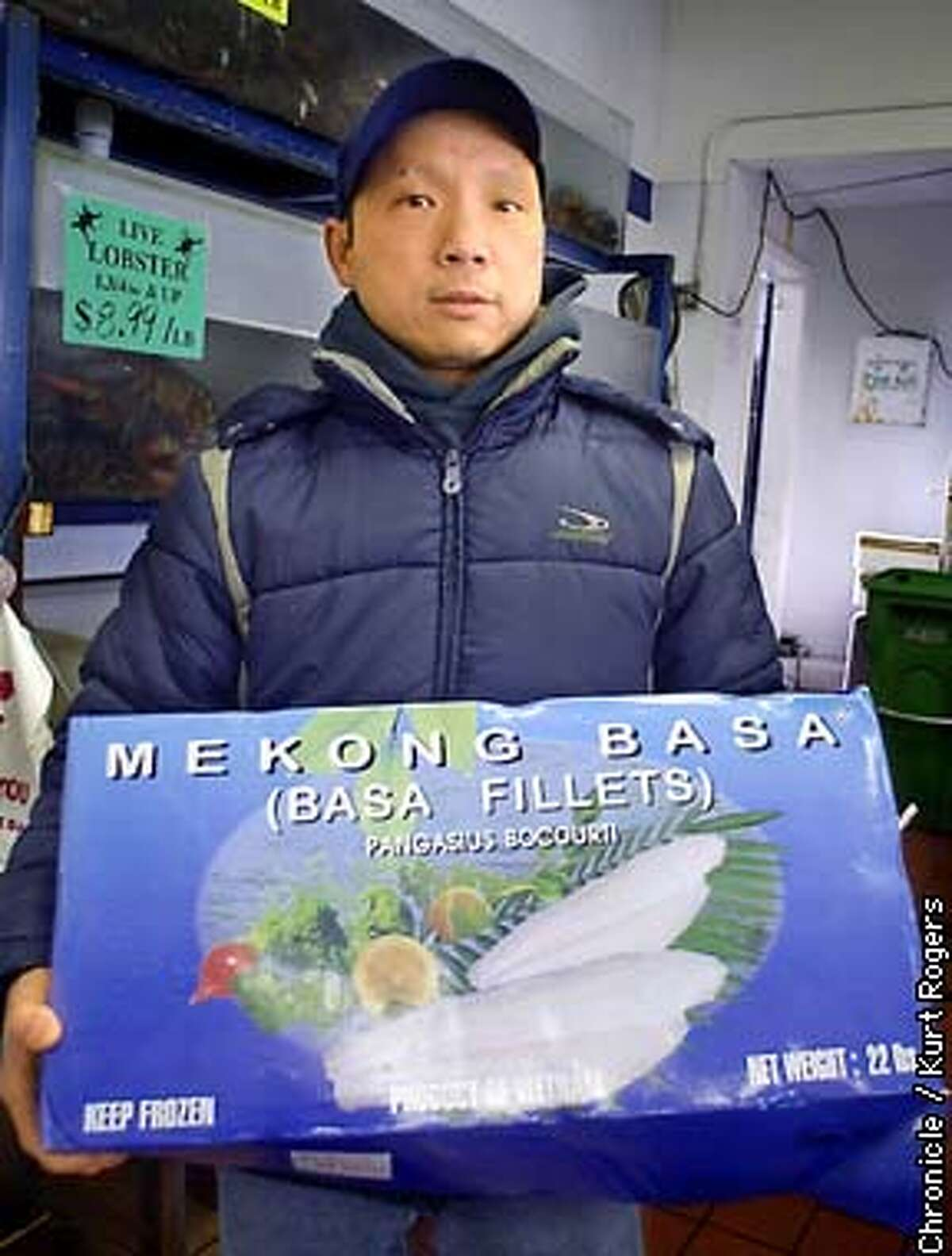 Minh Lam holds a box of Vietnamese Catfish at the Seafood Center on Clement st. The Fish are imported already filled. Photo By Kurt Rogers