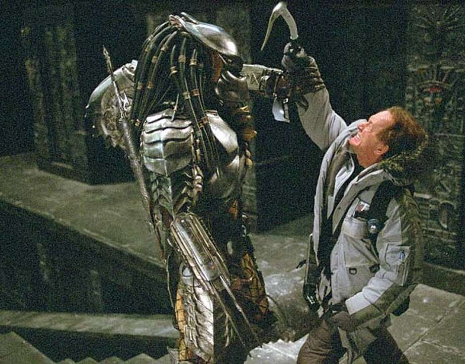 """Actor Lance Henriksen--as Charles Bishop Weyland--who represents an important casting connection with the """"Aliens"""" film franchise, battles the iconic monster from the thriller franchise """"Predator,"""" in a scene from """"Alien vs. Predator,"""" in this undated promotional photo. Henriksen, who played the android Bishop in the """"Aliens"""" and """"Alien 3"""" films, plays a present-day flesh and blood human in the new film that fuses the thrillers together. (AP Photo/Jurgen Vollmer, Twentieth Century Fox) Ran on: 08-14-2004  Beauty contest: At left, Predator (left) and Alien face off. Below, &quo;Aliens'' and &quo;Alien 3'' star Lance Henriksen plays a human, Charles Bishop Weyland, who battles the Predator. UNDATED Datebook#Datebook#SundayDateBook#11-14-2004#ALL#Advance##0422250780 Photo: JORGEN VOLLMER"""