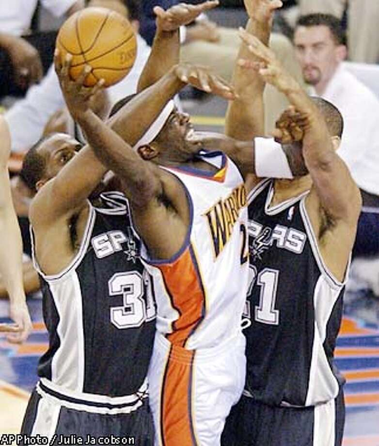 San Antonio Spurs' Malik Rose, left, and Tim Duncan, right, trap Golden State Warriors' Jason Richardson as he goes up for a shot during the first quarter Wednesday, Feb. 5, 2003, in Oakland, Calif. (AP Photo/Julie Jacobson) Photo: JULIE JACOBSON