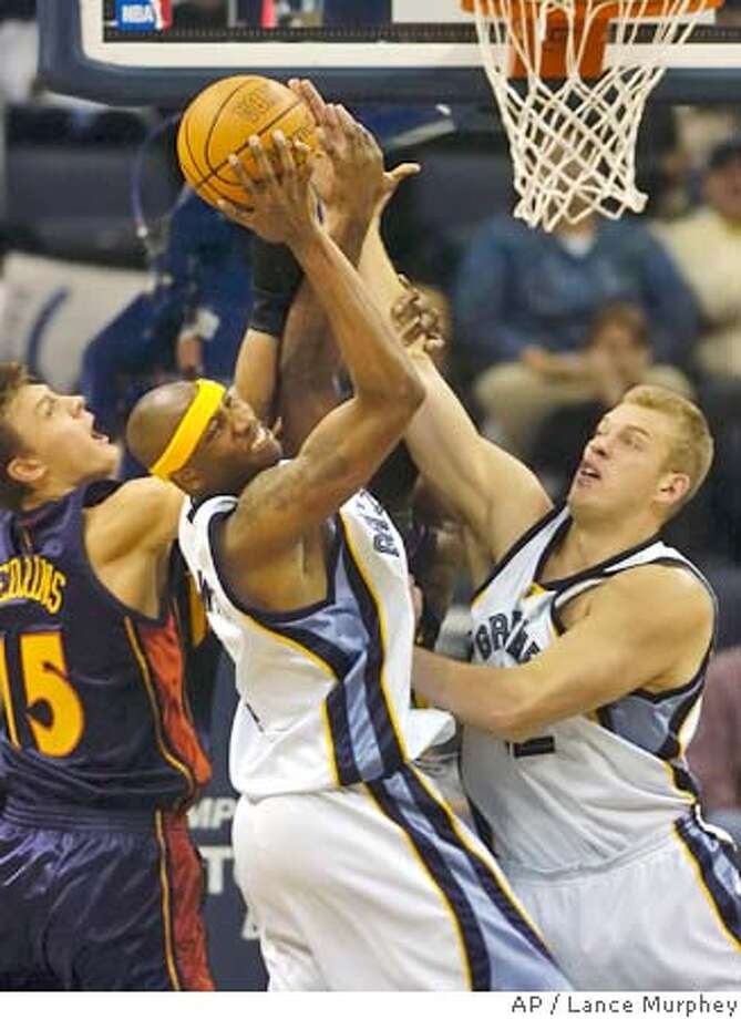 Golden State Warriors' Andris Biedrins of Latvia, left, fights for a loose ball against Memphis Grizzlies' Stromile Swift, center, and Jake Tsakalidis of Greece during the second half on Friday, Nov. 12, 2004 at the FedEx Forum in Memphis. The Grizzlies defeated the Warriors 96-67. (AP Photo/Lance Murphey) Photo: Lance Murphey