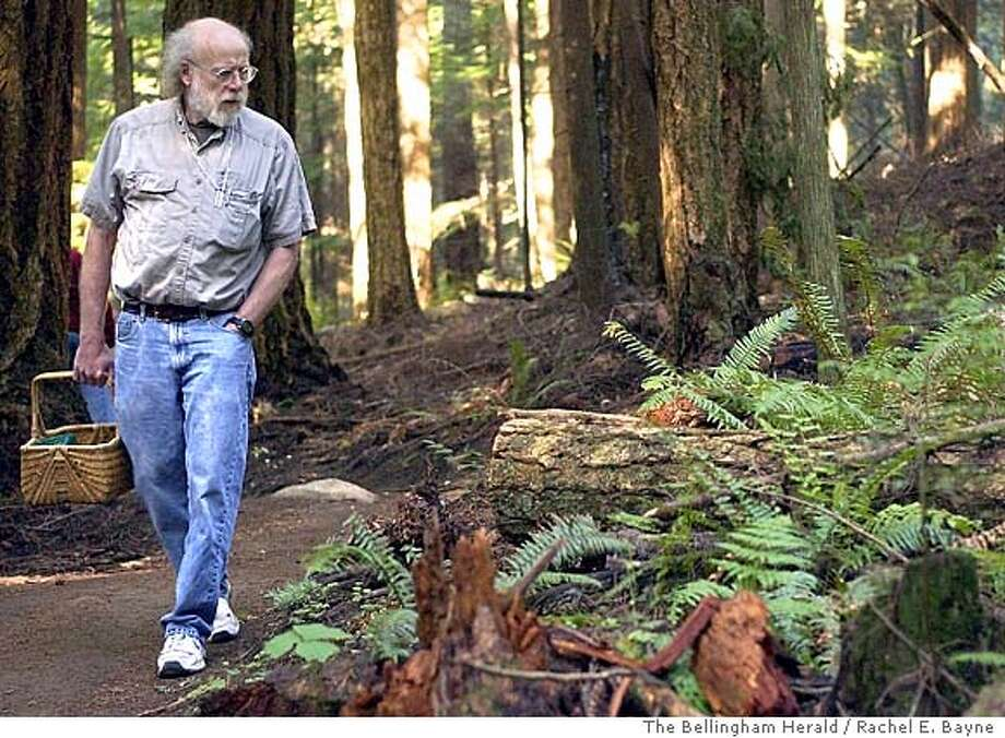 ** ADVANCE FOR WEEKEND, OCT 30-31 ** Fred Rhoades, a professor at Western Washington University who studies lichen and fungi, walks on a trail at the Stimpson Family Nature Reserve, Sept. 30, 2004, near Bellingham, Wash., while looking for different types of mushrooms. Experts, such as Rhoades, consider this a banner season for mushrooms. (AP Photo/The Bellingham Herald, Rachel E. Bayne) Photo: RACHEL E. BAYNE