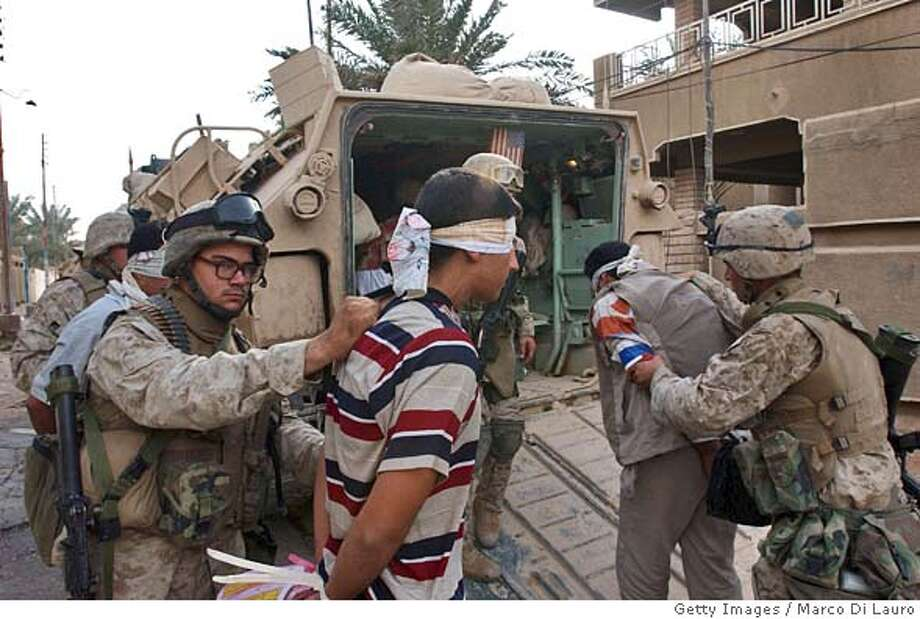 FALLUJAH, IRAQ - NOVEMBER 13: U.S. Marines from the 1st U.S. Marines Expeditionary Force, 1st Battalion, 3rd Marines Regiment, Bravo Company, lead arrested Iraqi men into an amphibious assault vehicle where they will then be brought to a detention center November 13, 2004 in Fallujah, Iraq. According to Iraqi National Security Adviser Kasim Dawood, 1000 insurgents have been killed and 200 insurgents have been captured during the six-day battle. U.S. Marines have been arresting males between the combat age of 15 and 55-years-old. (Photo by Marco Di Lauro/Getty Images) Photo: Marco Di Lauro