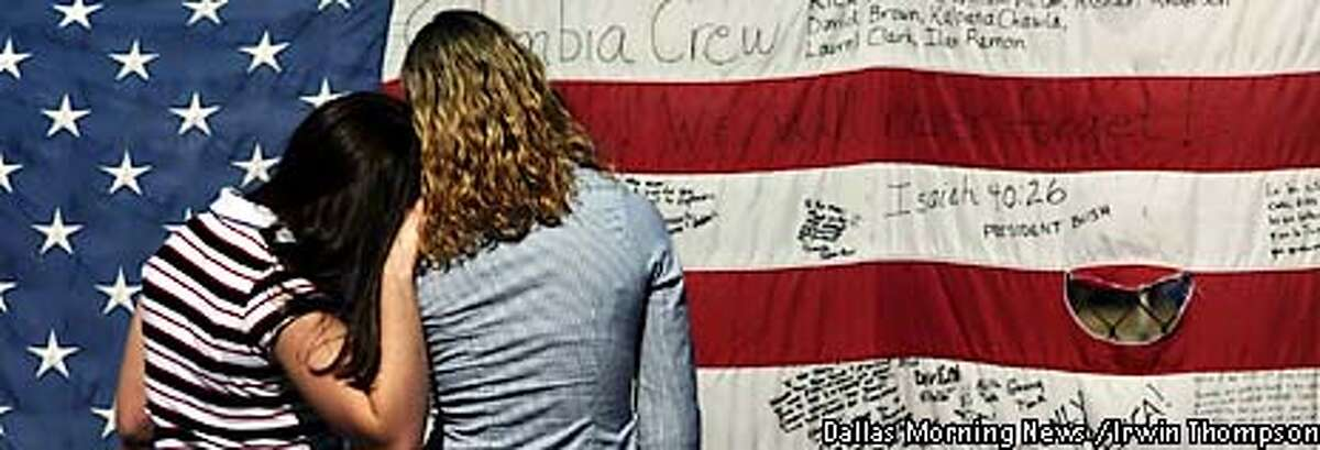 ** CORRECTS SPELLING TO JULIE, INSTEAD OF JUILE ** Clear Brook High School students Alyssa Varsos, 14, left, and Julie Martin, 15, right, read a flag at the makeshift memorial after the space shuttle Columbia memorial service at the Johnson Space Center in Houston, Tuesday, Feb. 4, 2003. (AP Photo/Dallas Morning News / Irwin Thompson)