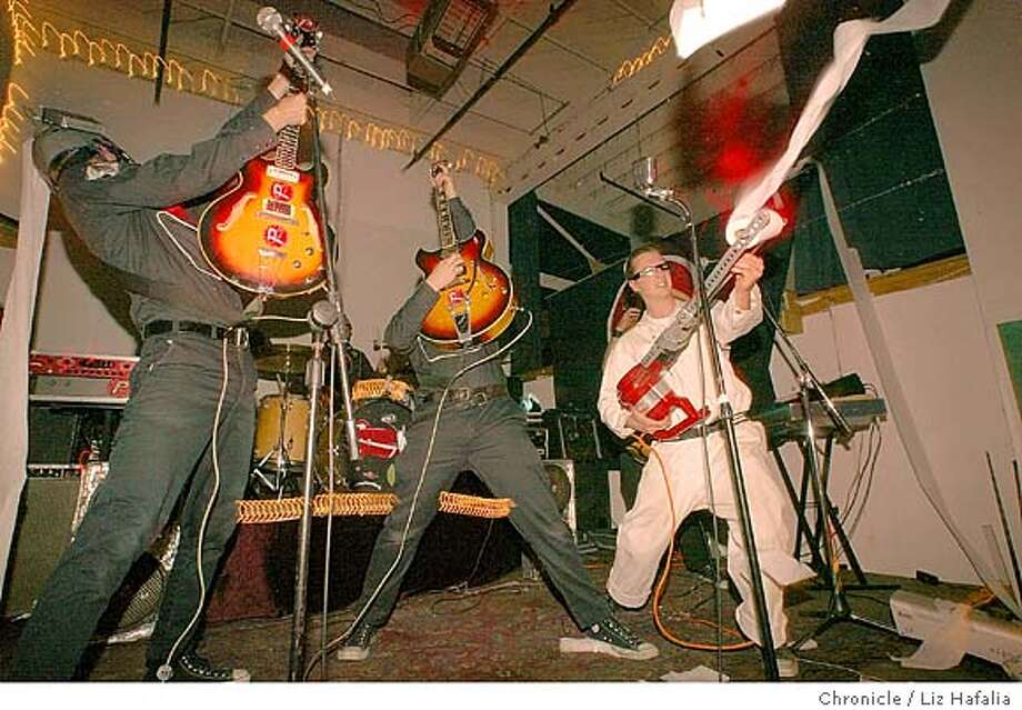 Musicians hosting a rock show in their Oakland warehouse space. Phenomenauts playing music and shooting toilet paper rolls into the crowd. Left to right--Corporal JoBot, Commander Angel Nova, and Professor Greg Arious. Shot on 4/26/03 in Oakland. LIZ HAFALIA / The Chronicle Photo: LIZ HAFALIA