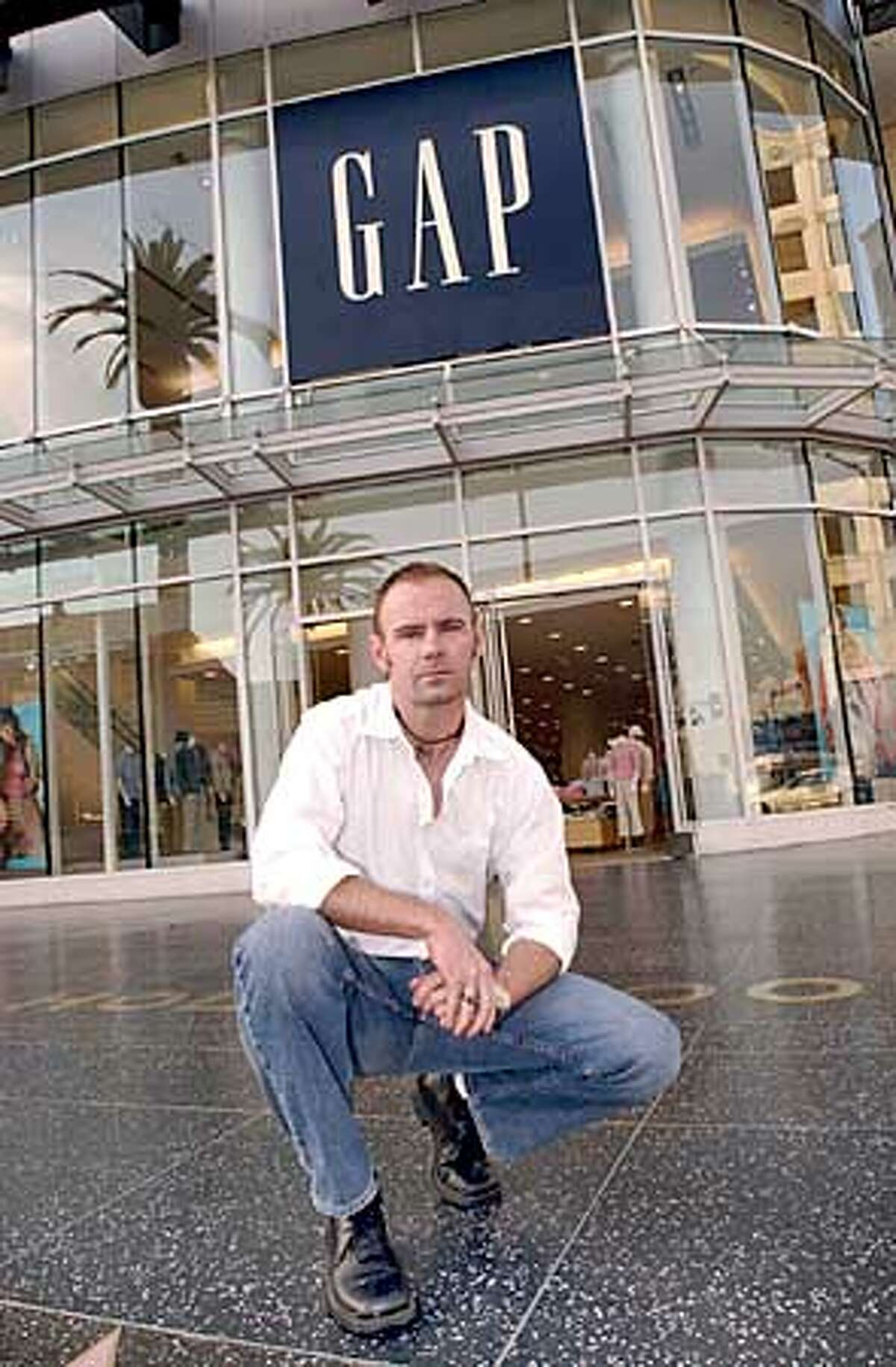 Robert Boleyn poses in front of a GAP store in the Hollywood section of Los Angeles, Tuesday, Feb. 4, 2003. Boleyn is wearing GAP pants, shirt, shoes and belt that he purchased in order to work one of the stores.