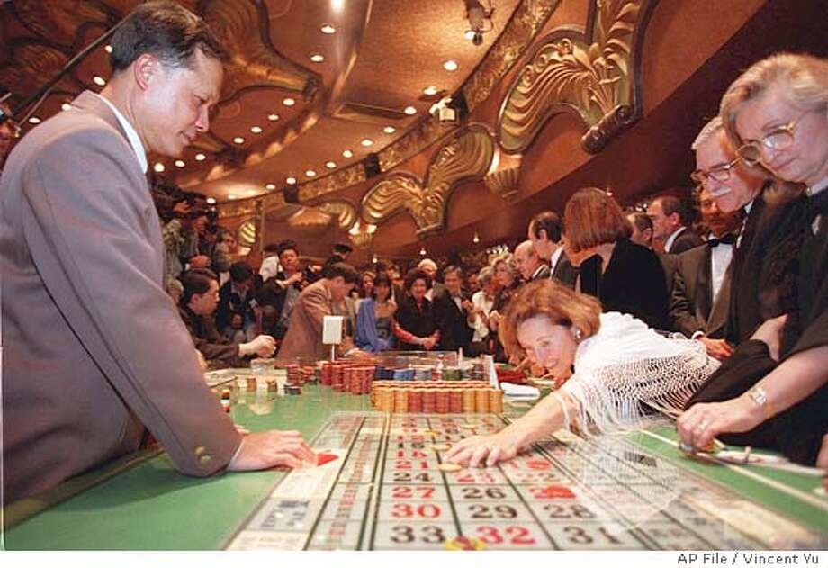 FILE--A woman places a bet on the roulette table at Casino Lisboa, the most famous and popular club in Macau, Feb. 15, 1999. Stanley Ho, the tycoon who has controlled Macau's lucrative casino trade since 1962, will be stripped of his monopoly next year, opening the way for competition in the tiny gambling haven, a Hong Kong newspaper reported Tuesday. (AP Photo/Vincent Yu/file) Ran on: 06-13-2004  Iberian flavor at Igreja de Sao Domingo (Church of St. Dominick). CAT Foreign#MainNews#Chronicle#11/11/2004#ALL#Advance#w4#422063252 Photo: VINCENT YU