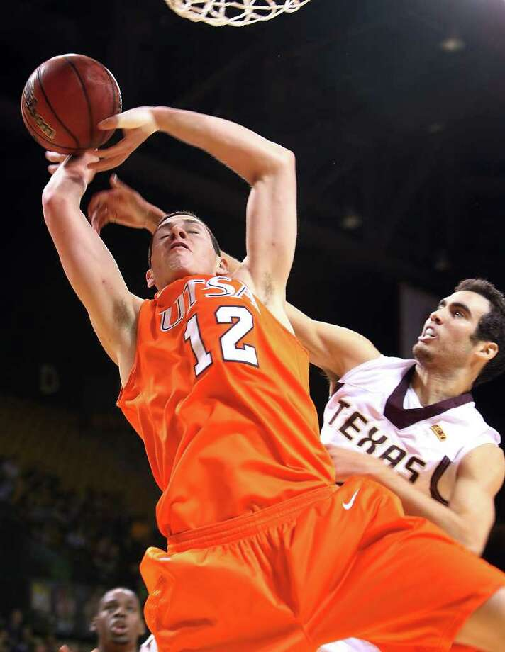 UTSA's Jeromie Hill (12) gets fouled by Texas State's Brook Ybarra (02) in men's basketball in San Marcos on Saturday, Jan. 21, 2012. UTSA defeated Texas State, 80-75. Kin Man Hui/San Antonio Express-News Photo: Kin Man Hui, ~ / San Antonio Express-News
