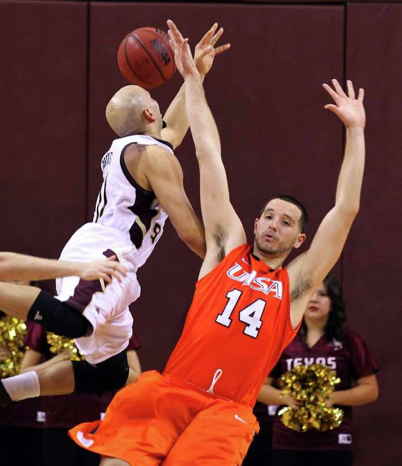 UTSA's Alex Vouyoukas (14) takes a charge from Texas State's Eddie Rios in men's basketball in San Marcos on Saturday, Jan. 21, 2012. UTSA defeated Texas State, 80-75. Kin Man Hui/San Antonio Express-News10 Photo: Kin Man Hui, ~ / San Antonio Express-News